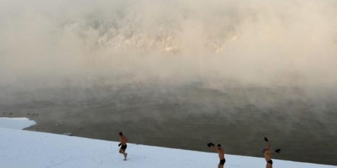 Enthusiasts of winter swimming warm up on the bank of the Yenisei River ahead of their weekly bathing session, with the air temperature at about minus 30 degrees Celsius (minus 22 degrees Fahrenheit), in the Siberian town of Divnogorsk, Russia November 18, 2016. REUTERS/Ilya Naymushin