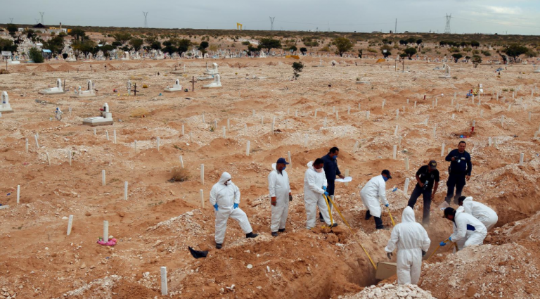 Mexican forensic workers bury unclaimed victims in a mass grave